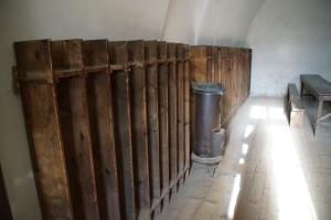 """The wooden shelves were the lockers where prisoners could put their shoes, """"clothes,"""" and their spoons.  The small little furnace was the only thing to heat the whole room (it was a fairly large room) and they were only rationed a bit of coal that obviously didn't last them very long."""